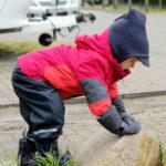Kind mit Vaude 3 in 1 Jacke klettert auf einen Stein